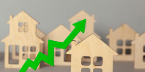 Concept of home buying trends represented by wooden houses and arrow