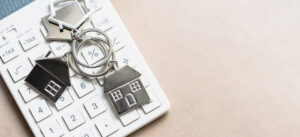 House key rings circling percent button, representing down payment for house and DPA loan